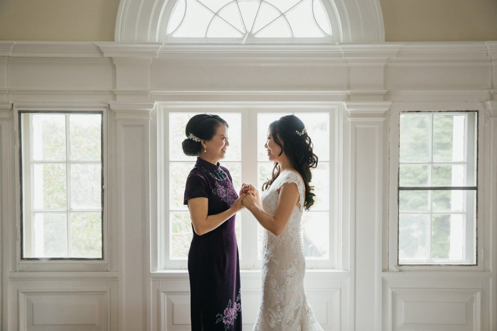 Bride and her mom holding hands during the getting ready at Bourne Mansion wedding