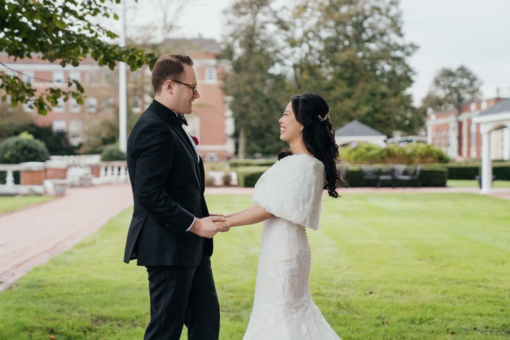 Bride and groom holding hands during a first look at Boune Mansion, Oakdale