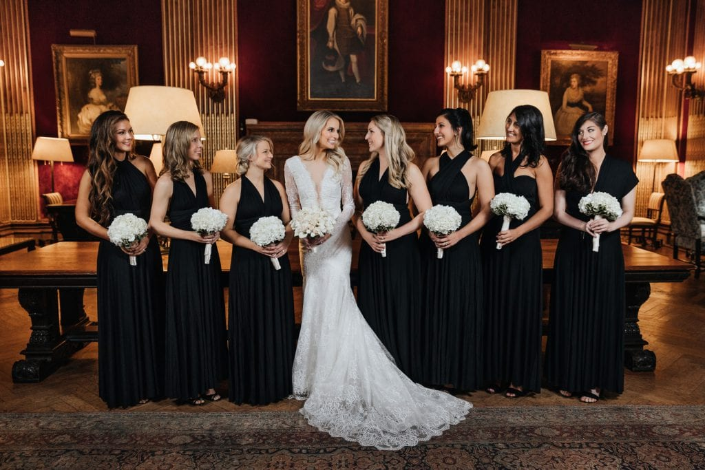 A portrait of a bride and bridesmaids standing in the Velvet room on a wedding day at the University Club of New York