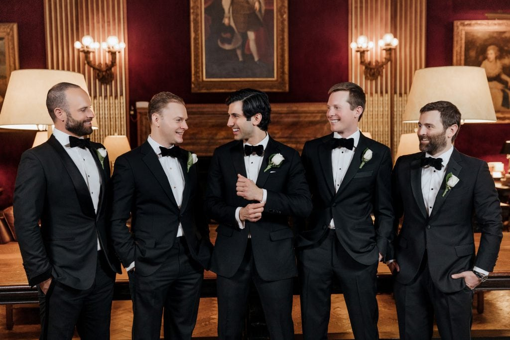 A portrait of a groom and groomsmen standing in the Velvet room