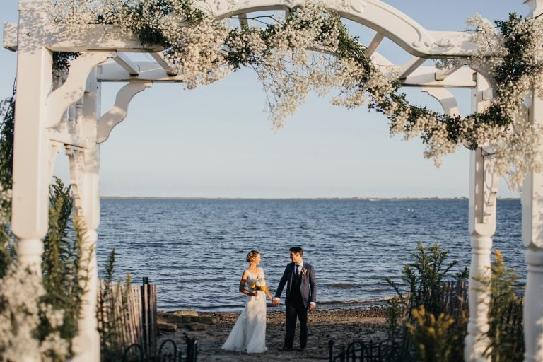 Bride and groom holding their hands during the portrait photoshoot near the water at Montauk wedding venue