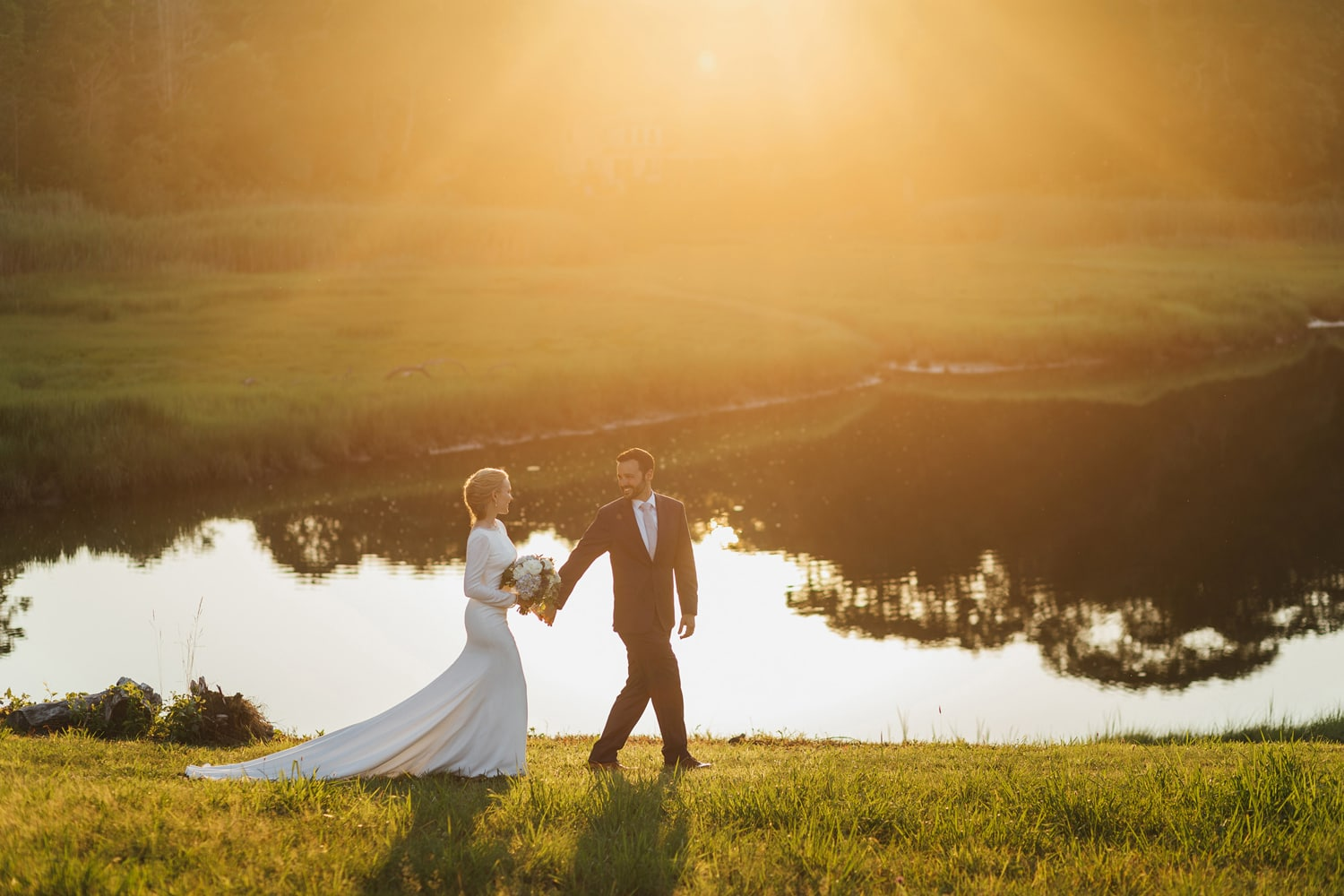 Bride and groom walking near the water at sunset