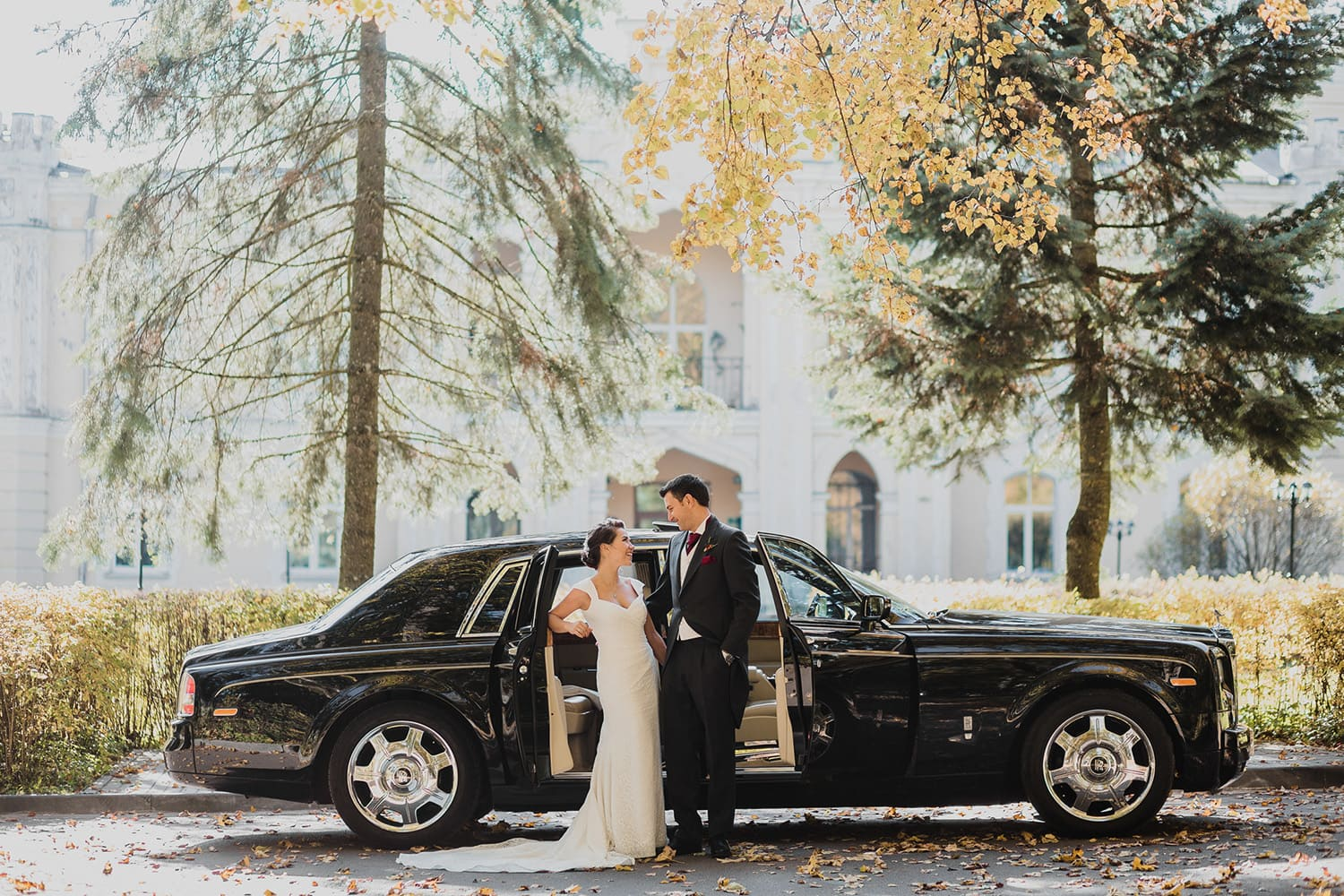 bride and groom posing near Rolls Royce car in front of the mansion in New Jersey