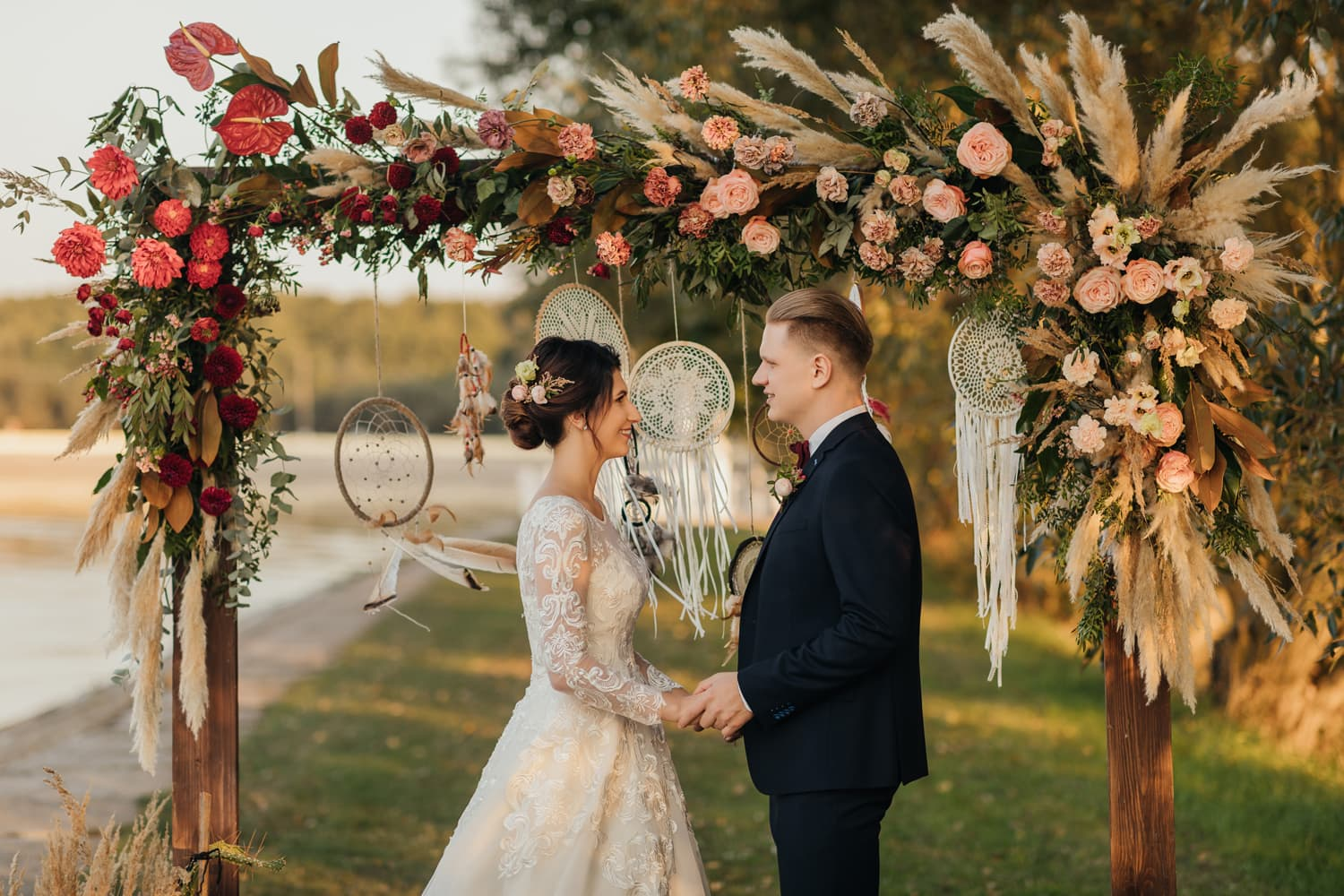 Bride and groom holding theirs hands during the wedding ceremony under the boho arch at waterfroте wedding venue in New Jersey