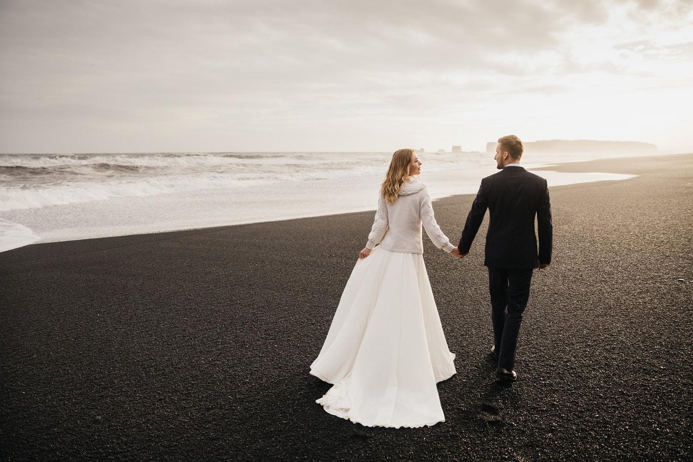 Bride and groom walking on Reynisfjara Black Sand Beach in Iceland