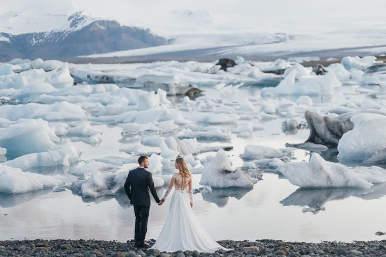 Bride and groom holding hands near Jokulsaron Iceberg Glacier Lagoon
