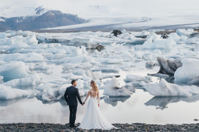 Bride and groom holding hands near Jokulsaron Iceberg Glacier Lagoon