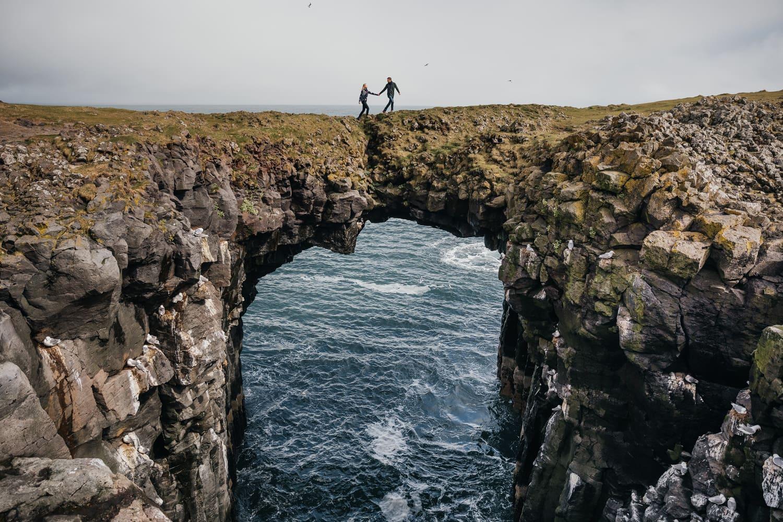 A couple walking across the Stone bridge in Arnarstapi, Iceland