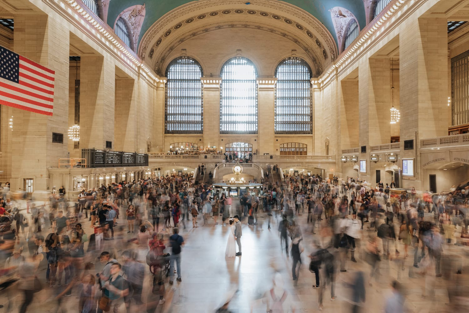 A bride and groom kissing in the middle of Grand Central Station
