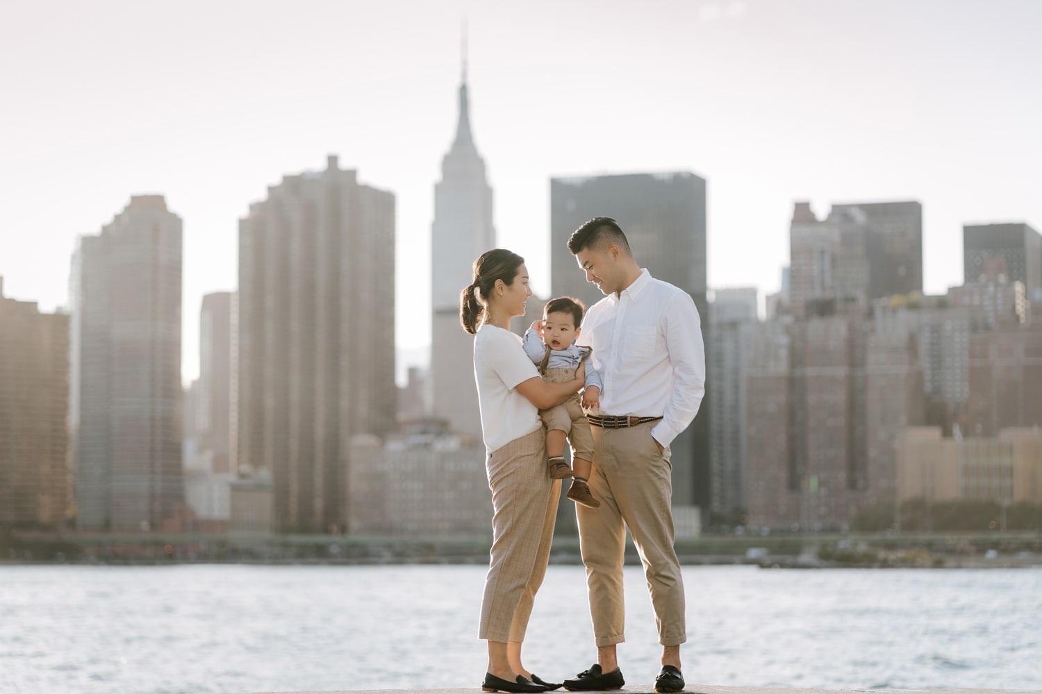 Family of three is posing at Gantry Plaza State Park with the midtown Manhattan skyline in the background