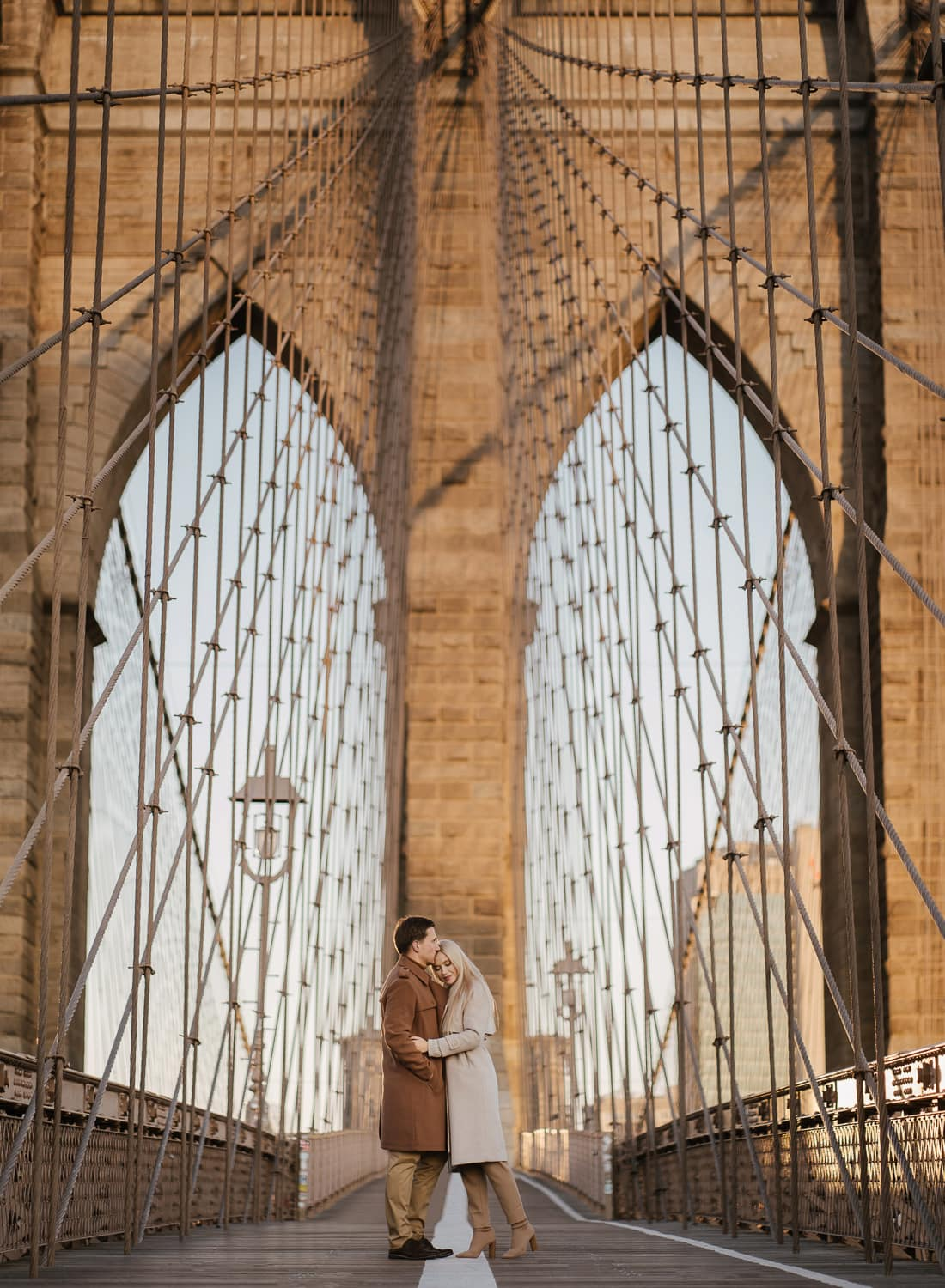 Couple posing during their engagement photoshoot on the Brooklyn bridge
