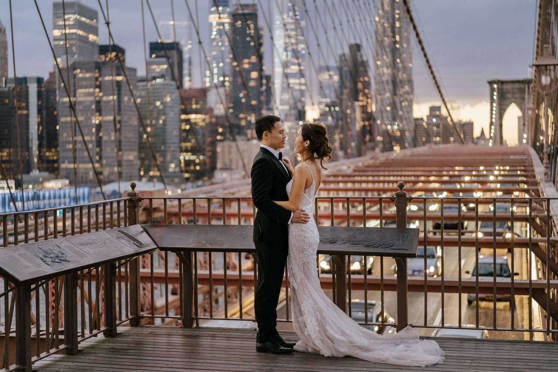 Couple posing during the Brooklyn bridge photoshoot with Manhattan skyline views