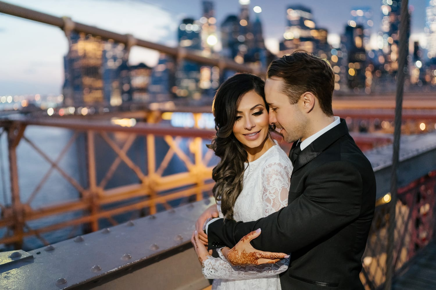 Couple posing during their night photoshoot on the Brooklyn Bridge with Manhattan skyline in the background