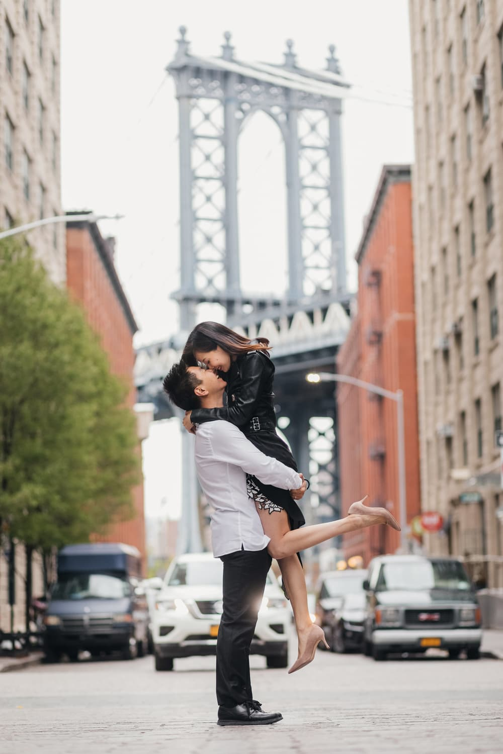 Couple posing during their engagement with Manhattan bridge view at the Washington street, Brooklyn